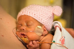 Preemie baby girl enjoying skin to skin with dad Stock Image