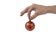 Preensão da esfera do Natal pela mão humana Fotografia de Stock Royalty Free