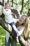 Preensão de sorriso da menina para a árvore foto de stock