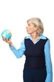 Preensão sênior da mulher um globo Imagem de Stock Royalty Free