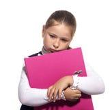 Preensão triste da menina da escola um livro foto de stock