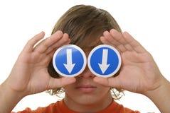Preensões do menino antes dos olhos da seta que especific para baixo Fotografia de Stock