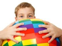 Preensões do menino na frente dsi mesmo esfera grande fotos de stock royalty free