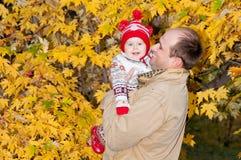 Preensões felizes do pai na filha pequena das mãos fotografia de stock