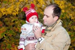 Preensões felizes do pai na filha pequena das mãos imagens de stock