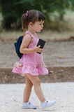 Preescholar girl in pink dress walking and holding a mobile phon Stock Photo