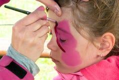 Preescolar del niño con la pintura de la cara Imagenes de archivo