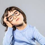 Preescolar serio con las lentes para el pensamiento, la imaginación, la confusión o el dolor de cabeza Fotos de archivo libres de regalías