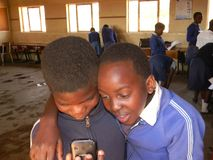 Preeteen primaire schoolkinderen die cellphone in klaslokaal doorbladeren stock foto's