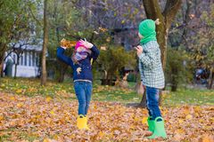 Kids play with maple leaves in park. Preeten boy and girl have fun at autumn stock image