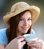 Preetty girl sips tea from English tea cup Stock Photography
