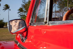 Preety teen on convertible car rear view mirror. Young woman in old red convertible car looking through rearview mirror Stock Photos
