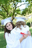 Preety Woman at Graduation. A pretty teenage woman hugging a friend and holding her diploma at graduation Royalty Free Stock Photos