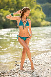 Preety woman in swimsuit near alpine river in early summer Stock Image