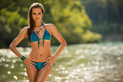 Preety woman in swimsuit near alpine river in early summer Royalty Free Stock Photo