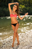 Preety woman in swimsuit near alpine river in early summer. Afternoon Royalty Free Stock Photo
