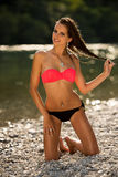 Preety woman in swimsuit near alpine river in early summer. Afternoon Stock Photo