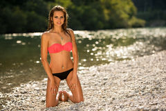 Preety woman in swimsuit near alpine river in early summer. Afternoon Stock Images