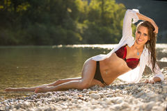 Preety woman in swimsuit near alpine river in early summer. Afternoon Royalty Free Stock Images