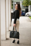 Preety woman walking in the city with bag in her hand Royalty Free Stock Photo