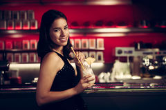 Preety young woman drinks cocktail in a night club. Young woman drinks cocktail in a night club Stock Image