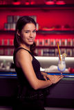 Preety young woman drinks cocktail in a night club Royalty Free Stock Image