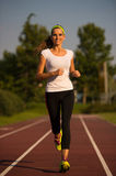 Preety young woman running on a track. On a summer afternoon Royalty Free Stock Photo