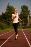 Preety young woman running on a track. On a summer afternoon Stock Image
