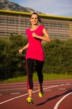 Preety young woman running on a track Stock Images