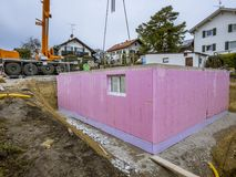 Prefabricated house, workers in setting up the basement walls. On building site royalty free stock photography