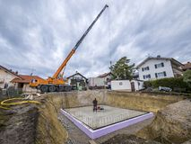 Prefabricated house, workers in setting up the basement walls. On building site stock images