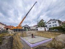 Prefabrykacyjny dom, pracownicy w utworzeniu piwnica izoluje obrazy stock