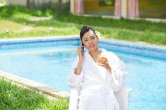 Prefect day by the pool. Lovely Vietnamese young woman sitting by the pool, drinking juice and talking on the phone Stock Photos