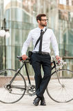 Preferred mode of transport. Full length of handsome young businessman leaning at his bicycle and looking away while standing outdoors Royalty Free Stock Image