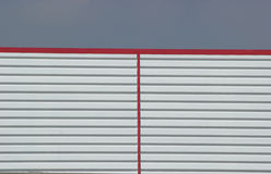 Preformed metal sheeting. Preformed metal sheeted wall with a red roof line Stock Image