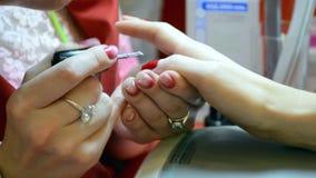 Prega o tratamento de mãos com o acryl vermelho no salão de beleza, filme