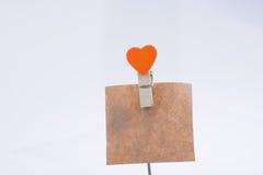 Pregador de roupa da forma do coração unido a um papel de nota Fotografia de Stock