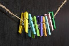Pregadores de roupa coloridos pequenos em uma corda Fotografia de Stock Royalty Free