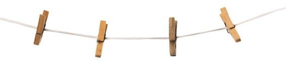Pregadores de roupa de madeira velhos em uma corda isolada no fundo fotografia de stock