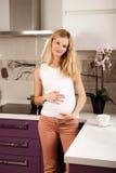 Pregannt woman in kitchen Stock Image