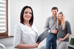 Pregant woman and her husband waiting for diagnosing in clinic. Royalty Free Stock Photo