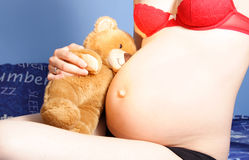 Pregant woman with teddy. Preganat woman sitting at her bed holding a teddy Stock Image