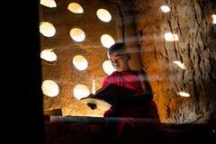 Pregare del monaco buddista Luce speciale fotografie stock
