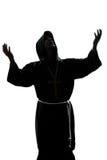 Pregare della siluetta del sacerdote del monaco dell'uomo Fotografie Stock Libere da Diritti