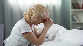 Pregare di signora di medio evo, sedentesi sul pavimento vicino al letto, alla fede ed alla speranza, religione immagini stock libere da diritti