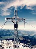 Pregare l'incrocio della sommità sull'alta montagna rocciosa Croce artistica d'acciaio sopra la montagna alpina Fotografia Stock