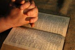 Pregare la bibbia delle mani fotografia stock