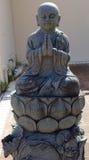 Pregare la statua del monaco buddista Fotografie Stock