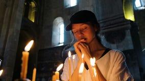 Pregare turistico della donna in una grande chiesa ortodossa stock footage