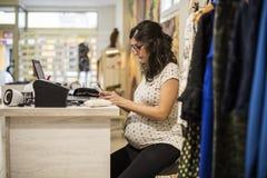 Pregenant-Frau, die im Kleidungsspeicher orking ist Stockbilder